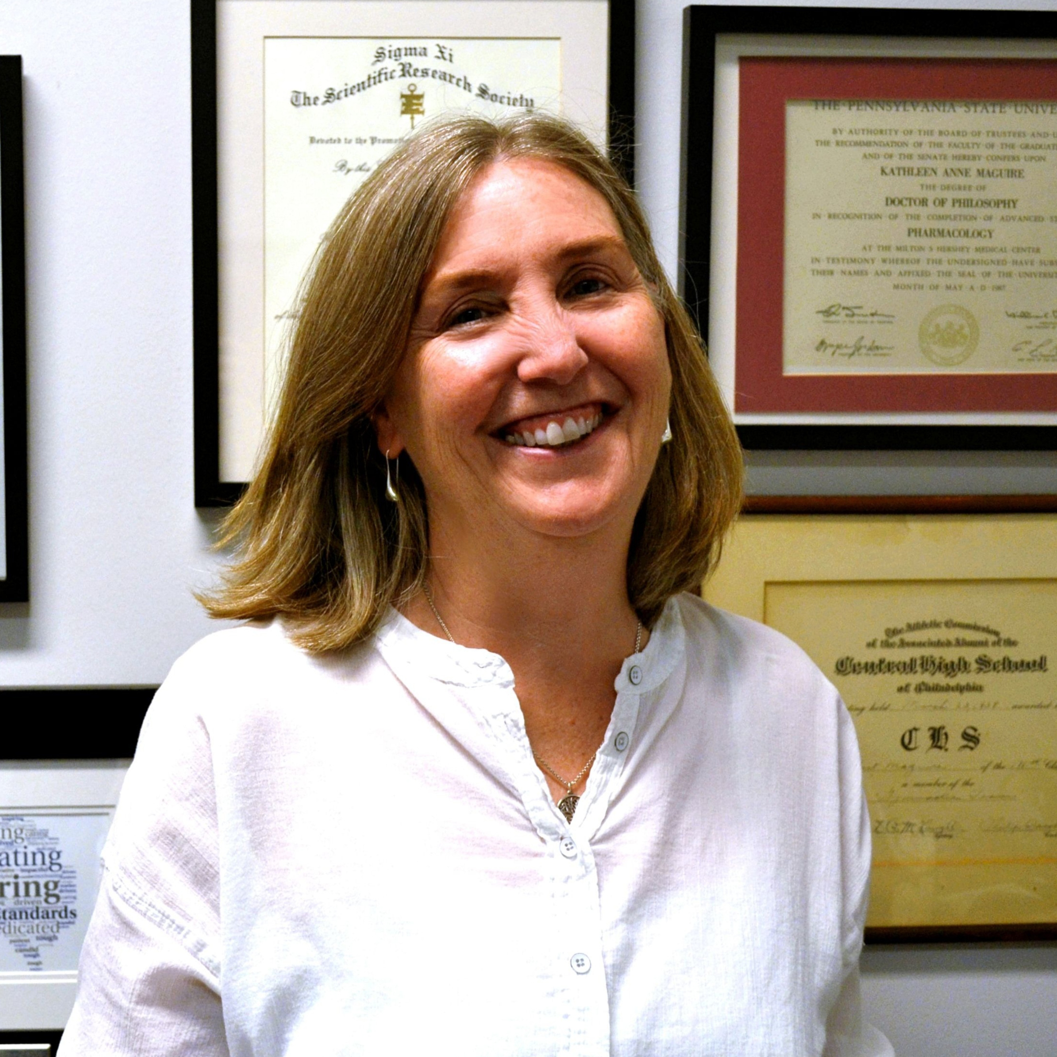 Headshot of Kathy Maguire-Zeiss in front of her wall of achievements.