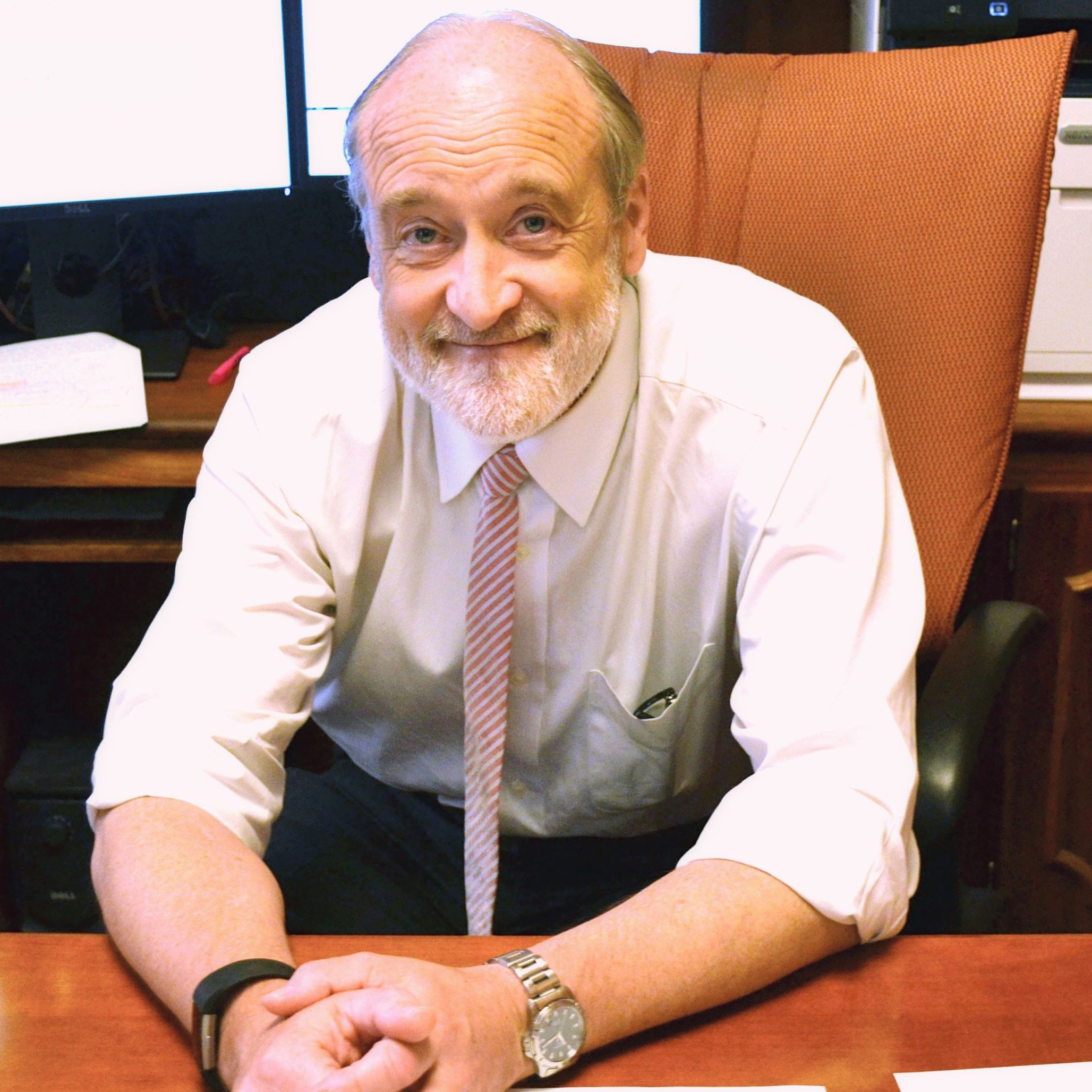 A photograph of Robert Clarke sitting in a chair in his office.