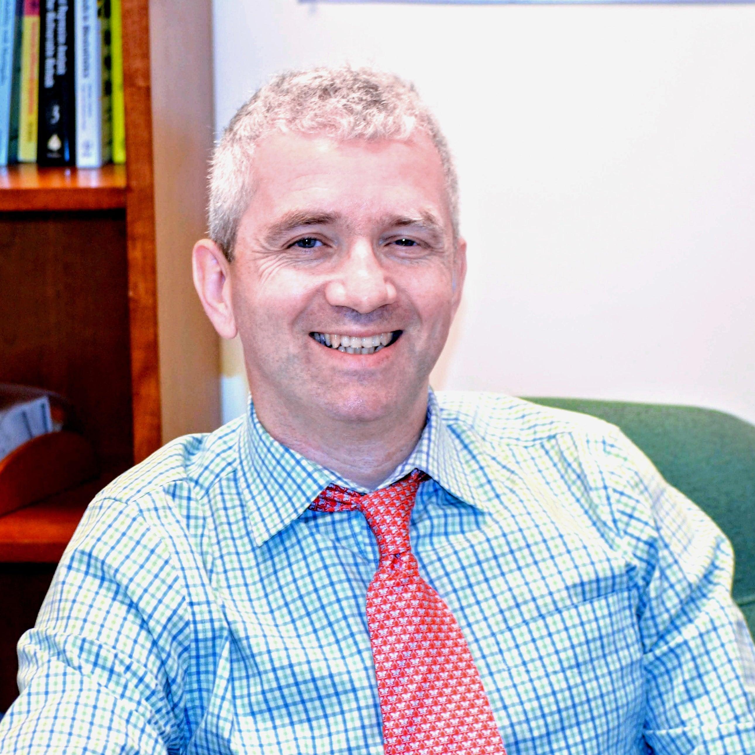 Headshot of Valeriy Korostyshevskiy sitting in his office.